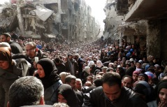 epa04101663 An undated handout picture made available on 26 February 2014 by the United Nation Relief and Works Agency (UNRWA) shows Palestinian and Syrian residents of Yarmuk Palestinian Refugee Camp crowding in a destroyed street as food is distributed, in Damascus, Syria.  EPA/United Nation Relief and Works Agency / HANDOUT  HANDOUT EDITORIAL USE ONLY/NO SALES